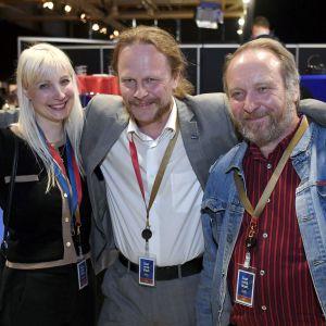 Laura Huhtasaari, Juho Eerola och Teuvo Hakkarainen firar med armarna om varandra.
