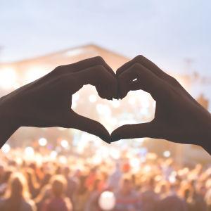 käsistä muodostuva sydän ja festariväkeä