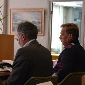 Två män sitter bredvid varandra i fullmäktigesalen.