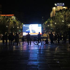 Människor följer med tv-rapporteringen från parlamentsvalet på Skanderbegplatsen i Tirana.