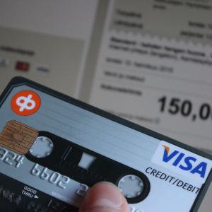 Luottokortti kädessä, verkkomaksun hinta taustalla tietokoneen näytöllä.