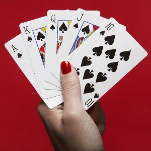 Naisen kädessä pelikortteja.