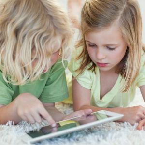 Två barn ligger på en vit matta och surfar på en pekdator.
