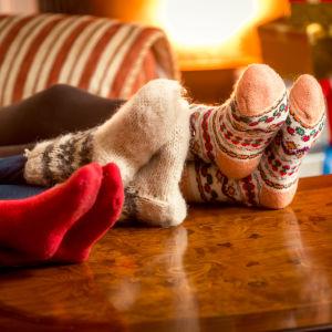 Tre personer sitter i soffan med fötterna i yllesockor som de vilar på bordet: En brasa och presentpaket finns i bakgrunden.