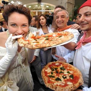 Savoijin kuningatar Margheritaksi pukeutunut nainen haukkaa nimeään kantavaa pizza margheritaa pizzakokkien ja yleisön ympäröimänä ko. pizzan 120-v-juhlassa Napolissa v. 2009.
