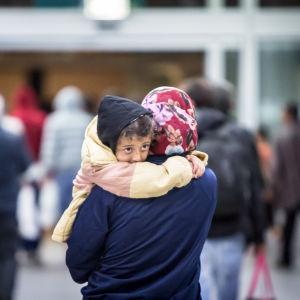 En asylsökande bär på sitt barn.