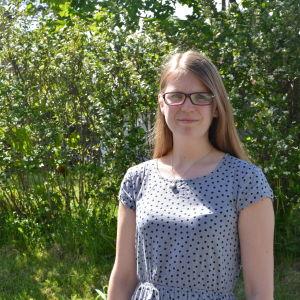 josefin holmlund står med grönska i bakgrunden