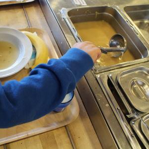 Lapsi ottaa ruokaa kuolussa.