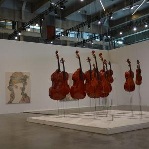 En konstutställning med ett konstverk gjort av stråkinstrument.