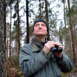 Fågelskådare spejar i skog.