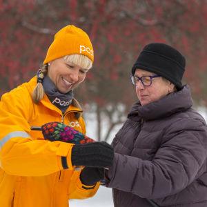 En kvinna klädd i postens kläder med postens logotyp hjälper en äldre kvinna att ta på sig sin handske.