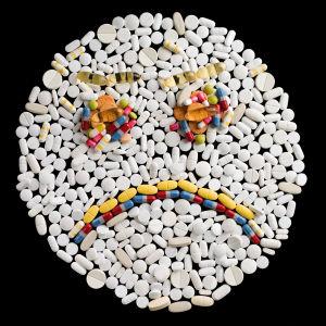 En bild av en sur gubbe, skapad av olika tabletter i olika färger.