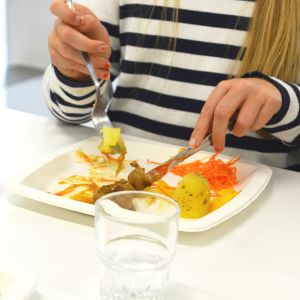En elev äter potatis och köttbullar på engångstallrik vid skollunchen.