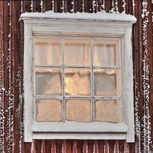 Ett frostigt fönster på en röd stuga.