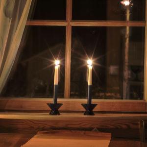 Två blåvita ljus brinner i ett fönster på kvällen.