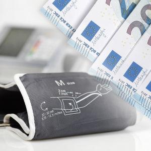 En blodtrycksmätare och ett antal 20 eurossedlar i en illustrativ bild.