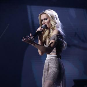 Ljushårig kvinna i grå klänning sjunger
