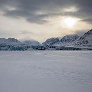 Aurinko pilviverhon takana lumisessa vuoristomaisemassa.
