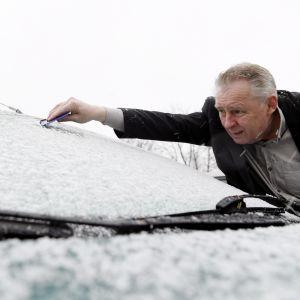 Man skrapar bort snö från bilens vindruta den 25.4.2017.