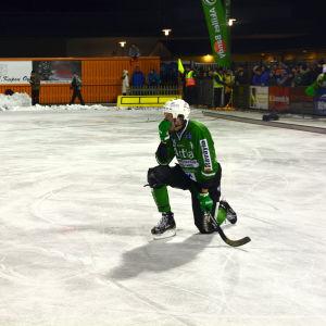 Bandyspelare på knä på isen