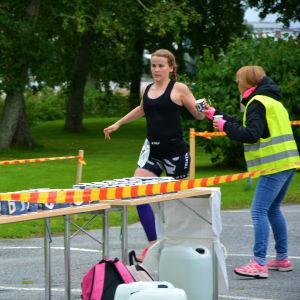 Triathleten Heidi Granholm tar emot en mugg vatten av en funktionär när hon springer