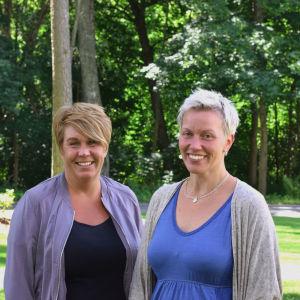 Två kvinnor står leende. I bakgrunden syns skog.