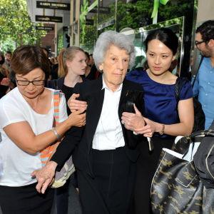En äldre kvinna får hjälp att evakueras under ett gisslandrama i Sydney. Man har evakuerat ett området i närheten av kaféet där gisslan hålls tillfångatagna.