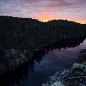 Auringonlasku Suomessa, kalliomaisema, havumetsä ja järvi.