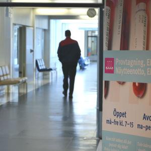 Man går i korridor på Vasa centralsjukhus förbi en affisch som pekar ut var provtagningen och laboratoriet finns.