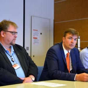 Ralf Holmlund, Stefan Damlin och Matti Latvakoski sitter vid ett bord och ser dystra ut.
