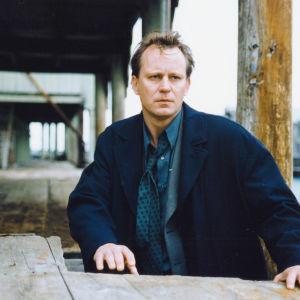 Stellan Skarsgård poserar i en nedlagd hamn.