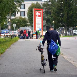 Triathlet leder sin cykel på väg mot anmälningen i Sun city triathlon i Vasa
