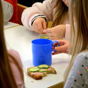 Barn äter en smörgås på ett daghem.