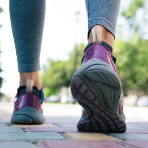 Två ben med löpskor tar ett steg.