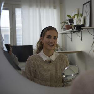ung kvinna ler mot spegeln
