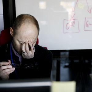 En arbetstagare masserar sin panna vid sitt arbetsbord.