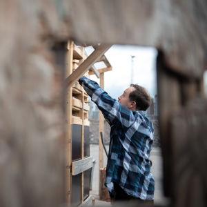Tuomas Tanner rakentamassa säilytylokeroita.