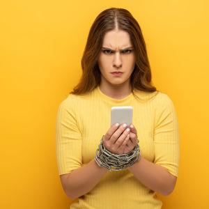 arg ung kvinna med telefon i handen blänger in i kameran