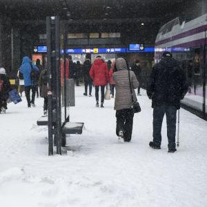 Paikallisjunia Helasingin rautatieasemalla, matkustajia