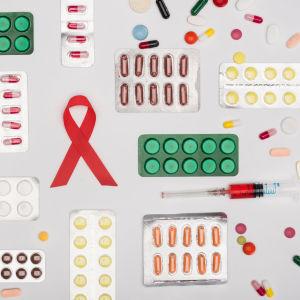 Grafik föreställande en aidsrosett, mediciner i pillserdform och en blodfylld spruta.