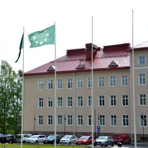 Flaggor framför stor stenbyggnad. Flaggorna gröna med vapen i form av vitsippor på. Träd och bilar vid byggnaden.