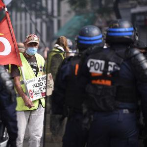 Keltaiseen liiviin pukeutunut mies, edessä rivi poliiseja selin kameraan.