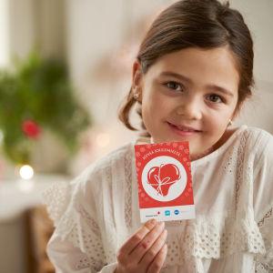 flicka håller i ett presentkort från Jul i sinnet-insamlingen
