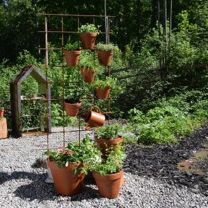 Örtkrukor i terrakotta är upphängda i ett armeringsnät.