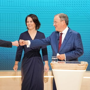 Två personer står bredvid varandra vid ett talarpodium. En av dem hälsar på en man som står nära med handen.