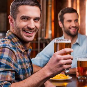Män som dricker öl på en pub och skrattar.