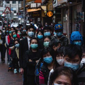 En lång kö med människor med ansiktsmask på en gata i en stad.