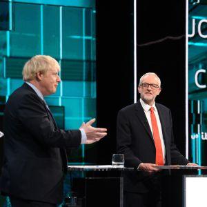 Boris Johnson och Jeremy Corbyn står på en scen vid varsitt bord under en debatt i Tonight's live.