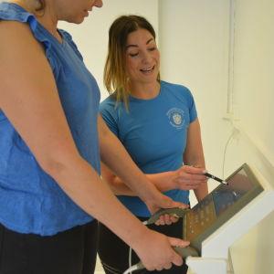En kvinna  pekar med penna på en skärm och ler, en annan står med sidan till vid en apparat som mäter kroppens fett, muskler med mera.