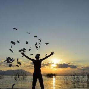 Person står och tittar mot en solnedgång i havet och kastar pengar runt omkring sig.